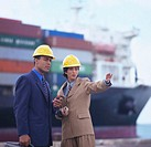 portrait of engineers wearing hardhats and standing in front of a cargo ship
