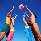 low angle view of a young couple and their children reaching up to catch a beach ball