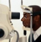 side profile of a man peering into a machine to check the eyes