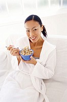 high angle view of a woman eating cereal from a bowl