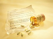 a crumpled suicide note with an open vial of medical pills