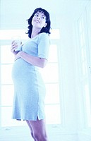 toned side profile of a pregnant woman standing with a glass of milk