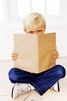 portrait of a boy (6-8) on the floor reading a book