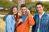 close up portrait of three teenage friends (16-18) one of which is talking on mobile phone