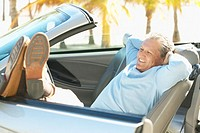 man relaxing in a convertible car with his feet leaning on the door