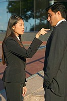 side view of a businesswoman poking a businessman with her finger