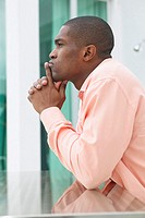 side view of a businessman sitting at a table looking thoughtful