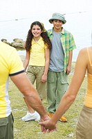close up of a couple holding hands with boy (11-12) and girl (10-11) in background