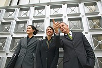 Low angle view of three business executives standing and businessman pointing his finger