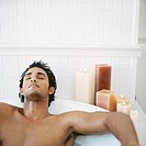 view of a young man soaking in a bathtub