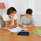Mother helping her son (11-12) with his homework