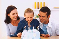 Portrait of a young couple looking at a birthday cake with their daughter (8-9)