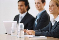 Smiling young business executives seated at a table