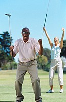 Young couple cheering after a round of golf