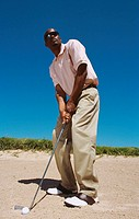 Low angle view of a young man readying to put from a sand pit on a golf course