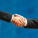 Low angle close-up of a handshake between a businessman and businesswoman