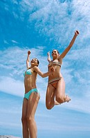 Low angle view of two young women jumping in bikinis
