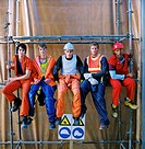 portrait of a group of construction workers sitting on metal scaffolding