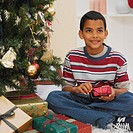 Boy (9-10) sitting beside a Christmas tree