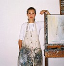 portrait of a painter in an apron standing beside an easel