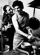 black and white view of a couple cooking together in a kitchen