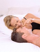Young couple lying on a bed smiling
