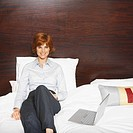 Front view portrait of businesswoman sitting on bed with laptop beside her