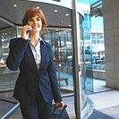 Close-up of businesswoman talking on mobile phone and holding luggage case