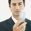 Front view portrait of businessman holding mobile phone