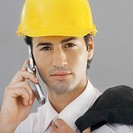 Front view portrait of businessman wearing hard hat and talking on mobile phone