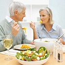Mature couple sitting at table and eating dinner