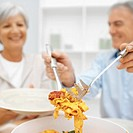 Mature man serving food to mature woman