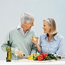 Side view of mature man cutting bell peppers and mature woman holding glass of wine