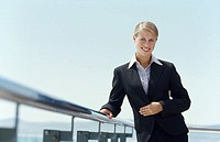 Front view portrait of businesswoman standing against railing