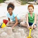 Front view of two girls sitting on sand making sandcastles (10-11)