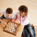 Elevated view of young couple playing game of chess