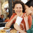 Close-up of young couple sharing drink in fast food restaurant