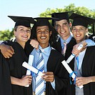 Front view portrait of four young people standing in a line wearing caps and gowns and holding certificates
