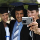 Front view portrait of three young people standing in a line wearing caps and gowns and taking photograph with camera