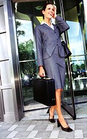shot of a young businesswoman exiting a building carrying a briefcase