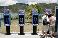 Pay phone, international telephone, couple. Road Town. Tortola. British Virgin Islands