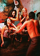 view of a group of women watching a shirtless man dancing for them