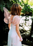view from behind of a girl (8-10) wearing angel wings and standing outdoors