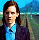 close-up of a business woman standing on railroad tracks