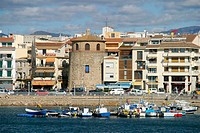 Fishing boats and tower by the port. Cambrils. Tarragona province. Catalonia. Spain