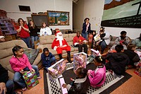 A Santa Claus volunteer distributes Christmas gifts to low income and homeless local children at a homeless shelter in Barstow, CA.