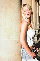 Young blonde woman posing in collonade in beautiful evening light.