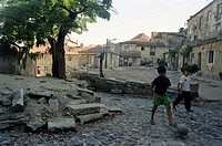Children playing football on a stone paved street