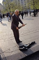 A man throwing money into street musician's bag