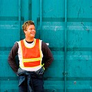 Young man laughing leaning against a cargo container